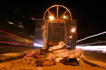A homeless Indian sleeps on a pavement in New Delhi