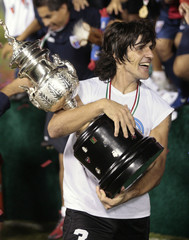 Atlante's captain Federico Vilar carries the trophy after his team defeated Pumas to win the Mexican league championship final in Cancun