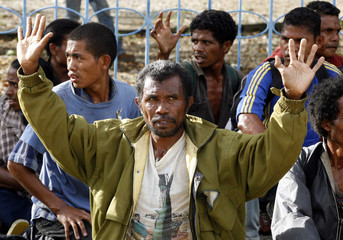 Militiamen sit with their arms raised after being detained by Australian peace keeping troops in Dili