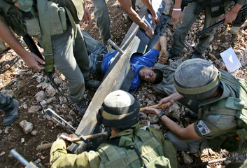 Israeli soldiers remove a Palestinian demonstrator chained to the ground during a protest against ...