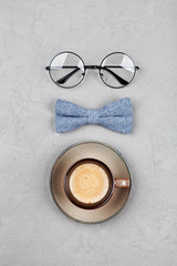 Happy Fathers Day background with morning coffee mug, glasses and bowtie on stone gray table top view in flat lay style.