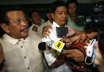 Former Philippine President Joseph Estrada(L) gestures to reporters after his criminal case hearing at the anti-graft court in Manila