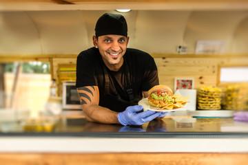 Smiling vendor with burger