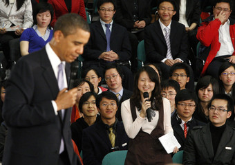 U.S. President Obama listens to a question from a woman during a town hall-style meeting with future Chinese leaders at the Museum of Science and Technology in Shanghai