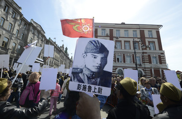 People hold pictures of World War Two soldiers as they take part in Immortal Regiment march during Victory Day celebrations, marking 72nd anniversary of victory over Nazi Germany in World War Two, in Vladivostok