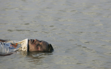 The body of an African would-be migrant lays at the beach of Mayfaa Hijr in southeastern Yemen