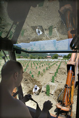 Workers prepare graves at a joint cemetery near the eastern town of Srebrenica