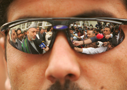 Afghan President Karzai is seen reflected in the sunglasses of a security guard in Kabul.