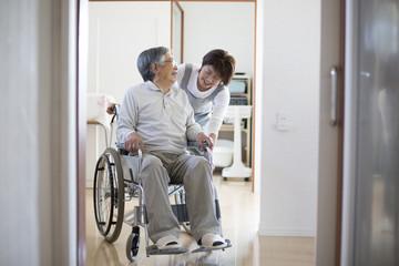 在宅介護、ヘルパーと車椅子の老人