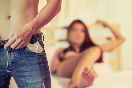 Man holding condom and sexy woman lying on bed.