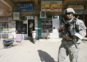 A U.S. soldier stands guard on a road during a joint patrol with Iraqi police in al-Mashtal district in Baghdad