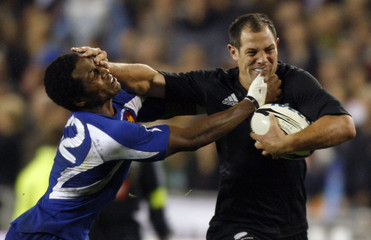 New Zealand All Black's Leon MacDonald fends off France's Ludovic Valbon during New Zealand's win in the first rugby test match at Eden Park in Auckland