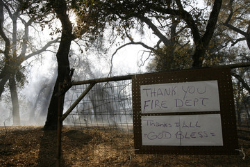 A sign thanks firefighters outside a home as smoke raises in the background from the Harris Fire near Jamul