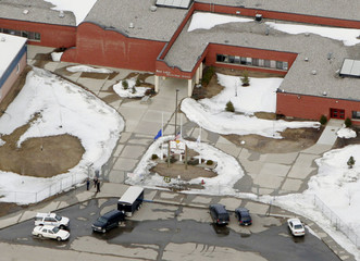 Police stand guard outside front doors of Red Lake Senior High School where shooting occurred.