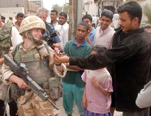 BRITISH SOLDIER PATROLLING BASRA IS GIVEN PINK FLOWER BY LOCAL IRAQI.