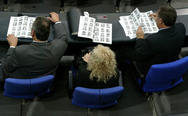 MEMBERS OF PARLIAMENT READ INDEX WITH PICTURES OF COLLEAGUES DURINGBUNDESTAG SESSION IN BERLIN.