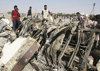 Residents stand near the wreckage of a truck used in a suicide bomb attack in Tikrit