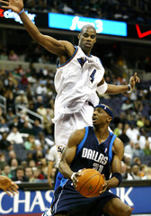 Wizards' Antawn Jamison is left in the air behind Terry of the Mavericks in Washington