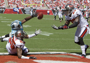Buccaneers defenders  Talib and Phillips fight with Panthers wide receiver Muhammad for the pass from Panthers quarterback Delhomme during the 1st half of their NFL football game in Tampa