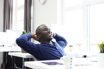 Relaxed Afro American business man sitting at his desk looking into the air.