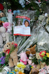Flowers and teddy bears surround the pictures of Nathalie and Stacy near the site where police found their bodies in Liege