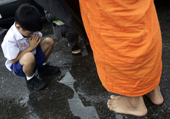A boy gives alms to a monk outside a Buddhist temple in Bangkok