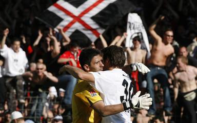 Eintracht Frankfurt's goalkepper Nikolov is hugged by Huggel following their German Bundesliga soccer match against Arminia Bielefeld in Bielefeld
