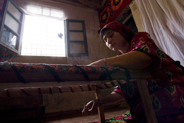 Woman embroiders cloth in traditional Tajik handicraft workshop in village of Padrud
