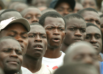 HAITIANS WATCH A RALLY IN GONAIVES.