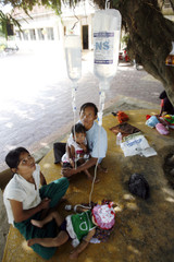 Children suffering from dengue fever are held by their parents under a tree outside a hospital in Cambodia's Kandal province