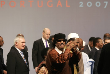 Libyan leader Gaddafi gestures after a family photo during their EU-Africa summit in Lisbon