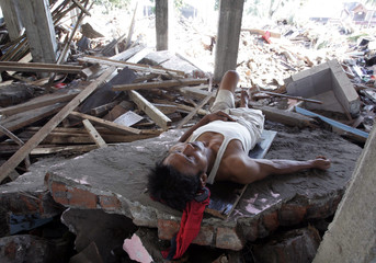 An Indonesian tsunami survivor takes a nap in his damaged house in Pangandaran