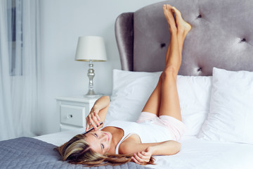 Relaxed woman with legs pointing up with cell phone on a bed at home