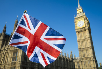 Bright view of United Kingdom flag flying in front of the Houses of Parliament at Westminster Palace in London, England, UK