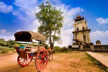 Horse Drawn Carriage parking in front of Nanmyin watchtower in Inwa ancient city, Mandalay Myanmar. Nanmyin watchtower is one of the most famous tourist destination in Mandalay.