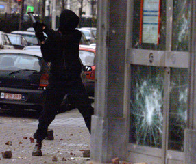 ANARCHIST DEMONSTRATOR SMASHES THE WINDOWS OF A BANK IN BRUSSELS.