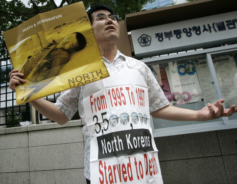 A human rights activist holds a sign showing a North Korean man who starved to death at a protest in Seoul