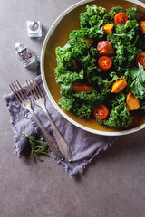 Kale salad sweet potatoes with onions and rosemary. Dark background.