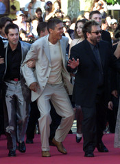 French director Luc Besson (R) runs with actors Frederic Diefenthal (L) and Sami Naceri (C) who star..