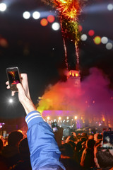 People holding their smartphones and photographing concert