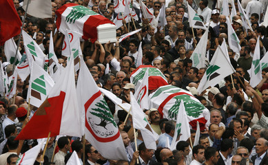 Supporters of the Christian Phalange party carry the coffins of assassinated anti-Syrian Christian legislator Ghanem and his two bodyguards during a funeral in eastern Beirut