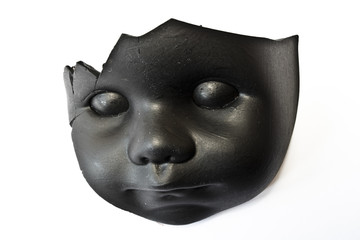 Broken Doll Head Painted Black on White Background