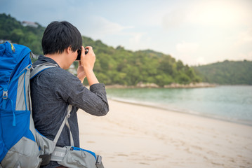 Young Asian backpacker man take photos of beautiful tropical beach and sea by camera, background for summer holiday, vacation time or travel photography concepts