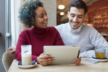 Beautiful African American girl and Caucasian guy staying in nice cafe with coffee and tea, watching funny media on screen of tablet PC. Woman is smiling looking at man and waiting for his reaction.