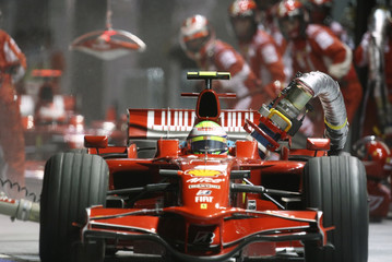 Ferrari Formula One driver Felipe Massa of Brazil drives off with the fuel hose still attached after a pit stop during the Singapore F1 Grand Prix at the Marina Bay circuit