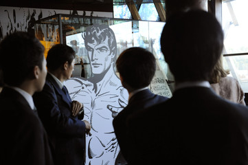 "Visitors look at comic strips during the exhibition ""Tarzan!"" at the Quai Branly Museum in Paris"