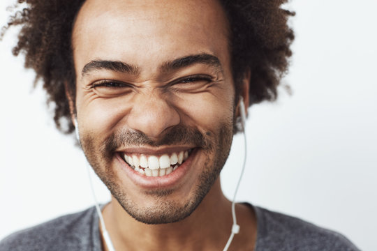 Close up portrait of young happy african man smiling listening to upbeat streaming music laughing over white background. Youth concept.
