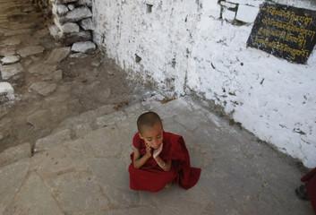A young Buddhist monk waits for spiritual leader the Dalai Lama at a monastery in Tawang