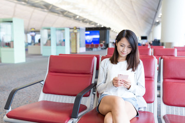 Woman using mobile phone in the airport