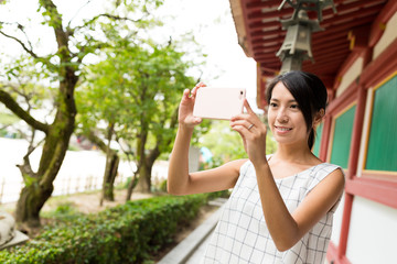 Woman taking photo with cellphone in Japanese temple